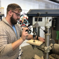 Sean McCormack, the founder of Art Aggregate, uses a drill press to carve a handle into a charcuterie board in the workshop (Amanda Pope/Generation Z).